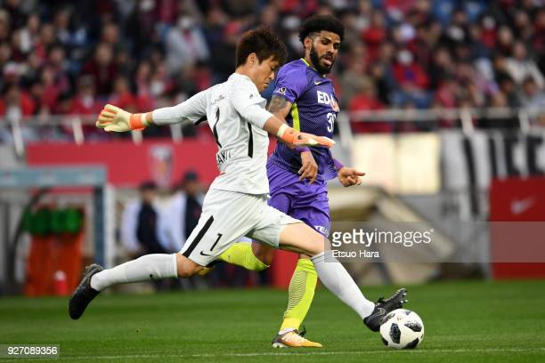 Shusaku Nishikawa of Urawa Red Diamonds and Patric of Sanfrecce Hiroshima compete for the ball during the JLeague J1 match between Urawa Red Diamonds...