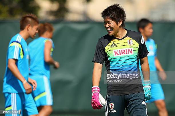 Shusaku Nishikawa shares a laugh with a team mate during a Japan training session at North Greenwood Recreation Aquatic Complex on June 4 2014 in...