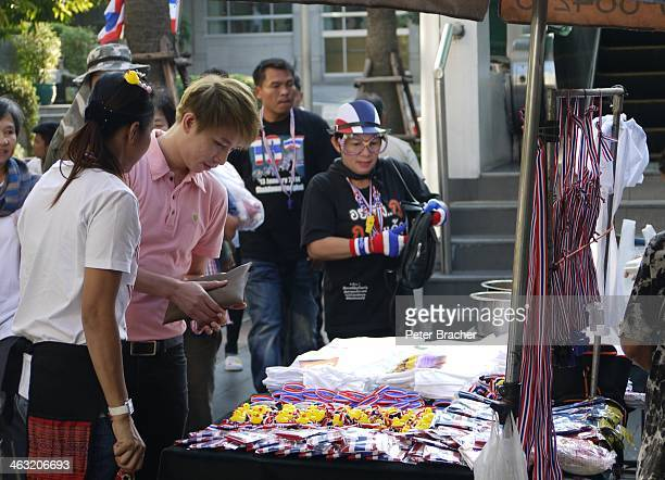 Shutdown Bangkok 13 January 2014 - Anti-government protests in central Bangkok Buying the red, white and blue Thailand protest souvenirs in a street...