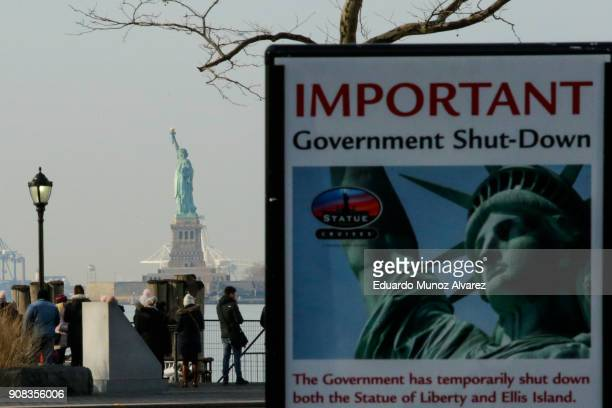 Shutdown placard is seen at the entrance of the Liberty State ferry terminal as people look on in Battery Park on January 21, 2018 in New York City....