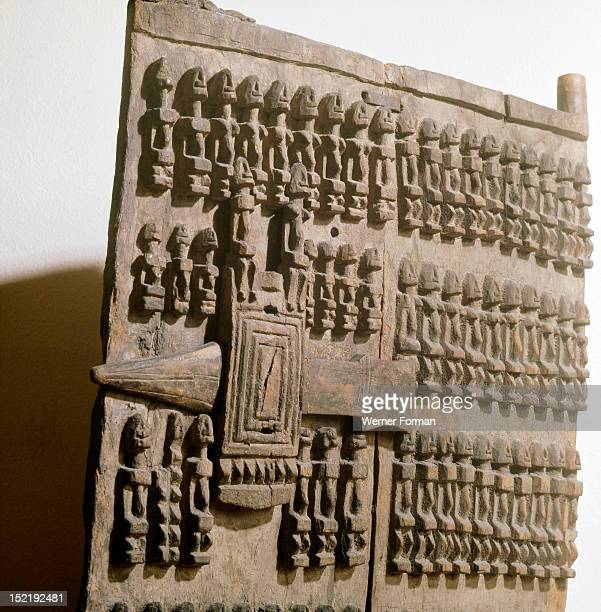 A shutter like door with lock from a Dogon granary sculpted with rows of figures which may refer to the founding ancestors of the owners family or...