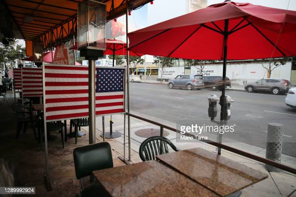 Shuttered outdoor restaurant seating is decorated with American flags on the first day of new stay-at-home orders on December 7, 2020 in West...