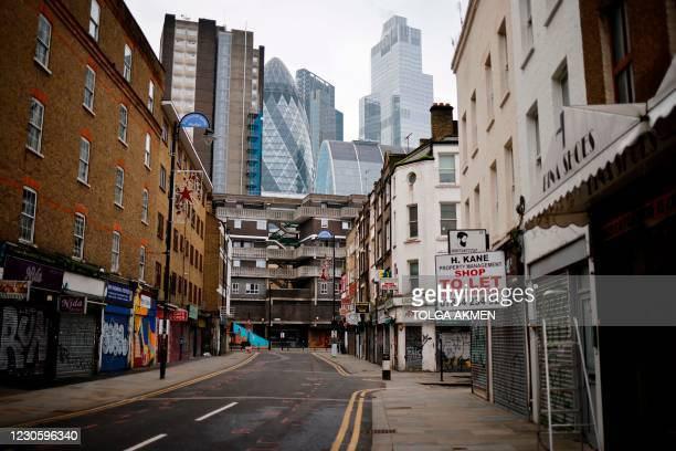 Shuttered shops are seen along deserted streets in the City of London on January 15 during the third coronavirus lockdown. - Britain's economy...