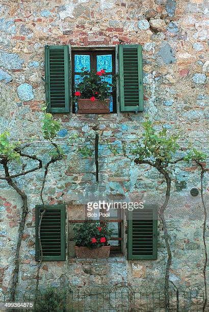 Shuttered windows, flower boxes on stone building