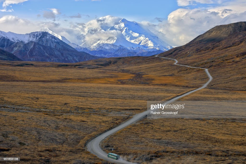 Shuttle bus driving on park road with Mount Denali in background : Stock-Foto