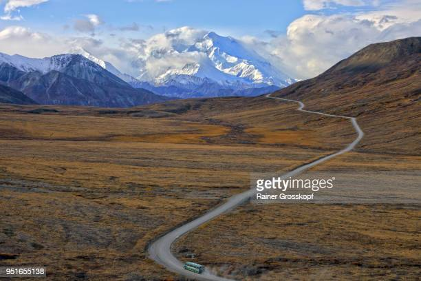 shuttle bus driving on park road with mount denali in background - rainer grosskopf fotografías e imágenes de stock