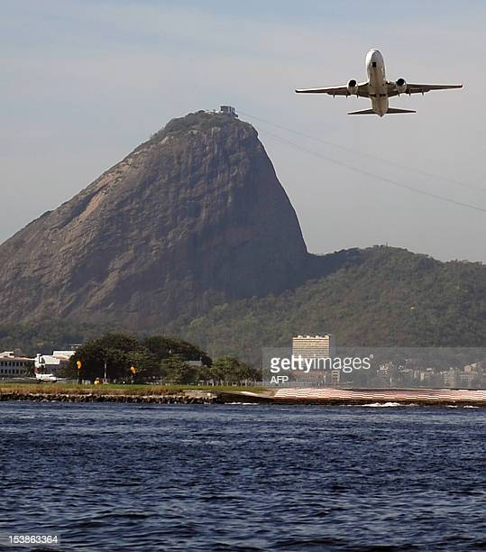 A shuttle service airliner takes off from the Santos Dumont domestic airport with the Sugar Loaf landmark on the background in Rio de Janeiro on...
