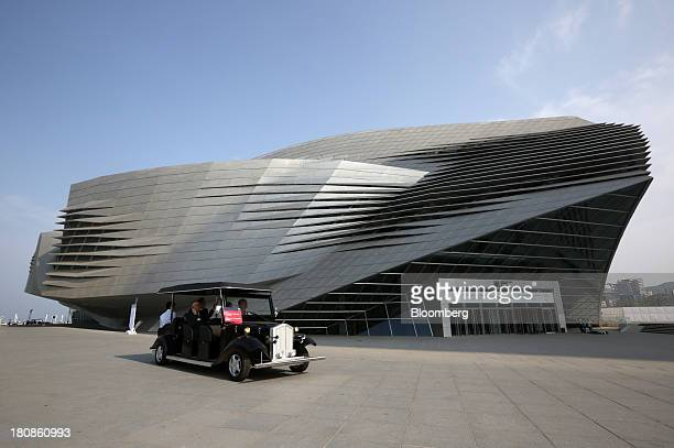 A shuttle vehicle drives past the Dalian International Conference Center at the Dalian Wanda Center in Dalian China on Friday Sept 13 2013 Goldman...