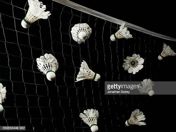 Shuttlecocks stuck in net, against black background