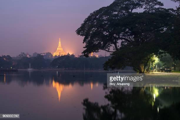 Shwedagon pagoda look through Kandawgyi lake before sunrise in Yangon, Myanmar.