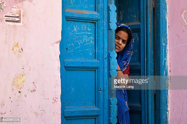 Shy and curious woman hiding behind a blue door in the city of Mathura in Uttar Pradesh, India.