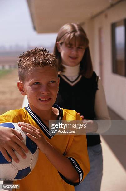 Shy Boy Holding a Soccer Ball in Front of a Girl