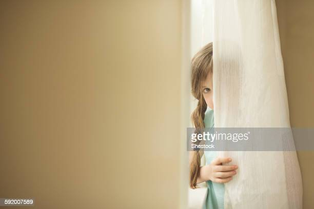 shy caucasian girl peeking around curtain - escondendo - fotografias e filmes do acervo