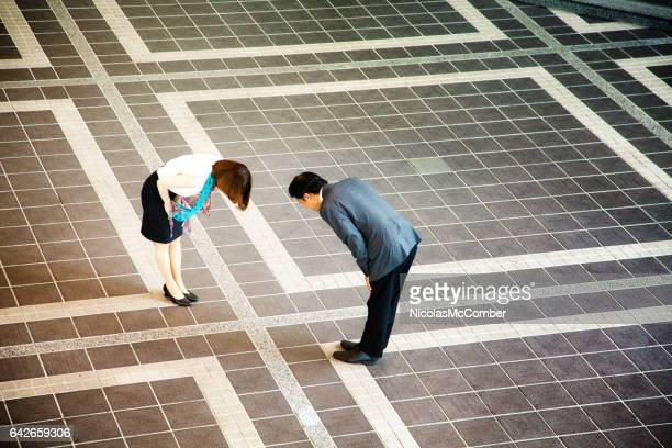 shy japanese businesswoman bowing as she meets colleague - humility stock pictures, royalty-free photos & images