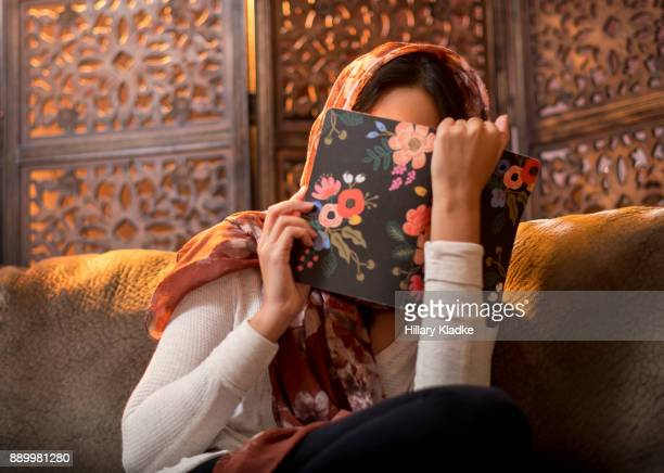 Shy Muslim woman hides face with book
