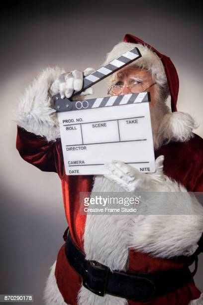 Shy Santa Claus holding a film clapperboard to cover his face up