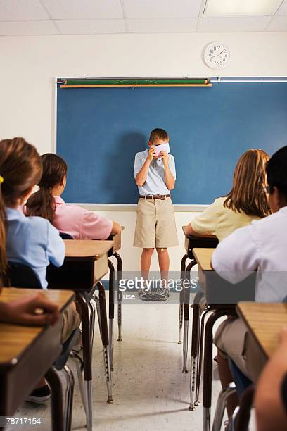 Shy Student Hiding Behind Note Cards During Class Presentation
