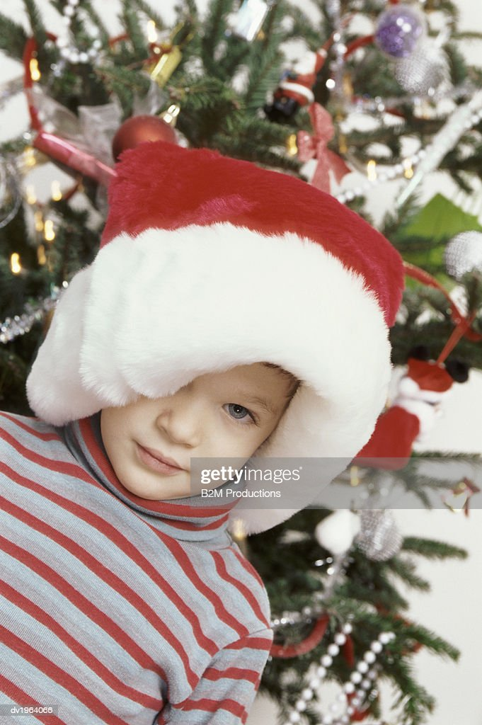 Shy Young Boy Wearing a Big Santa Hat Standing in Front of a Christmas Tree : Stock Photo