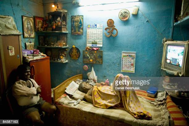 Shyan Natekar and his father Rajan Natekar watch television in their dwelling in the Dharavi slum on February 2 2009 in Mumbai India The...