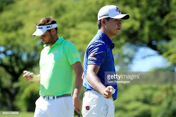 Si Woo Kim of South Korea and Jeff Overton react on the fourth green during the final round of the Sony Open In Hawaii at Waialae Country Club on...