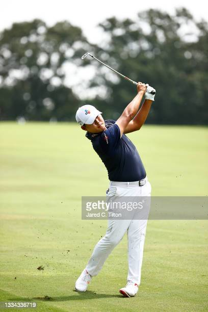 Si Woo Kim of South Korea plays an approach shot on the 18th hole during the final round of the Wyndham Championship at Sedgefield Country Club on...