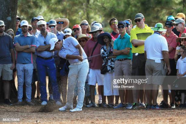 Si Woo Kim of South Korea plays from the pine straw on the tenth hole during the final round of THE PLAYERS Championship at the Stadium course at TPC...