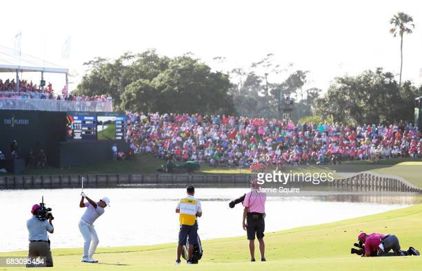 Si Woo Kim of South Korea plays his second shot on the 18th hole during the final round of THE PLAYERS Championship at the Stadium course at TPC...