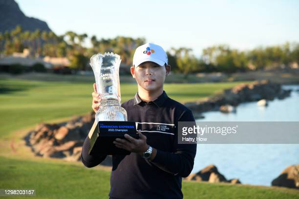 Si Woo Kim of South Korea poses with the trophy after putting in to win on the 18th green during the final round of The American Express tournament...