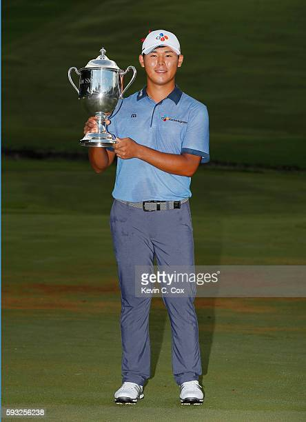 Si Woo Kim of South Korea poses with the trophy after winning the final round of the Wyndham Championship at Sedgefield Country Club on August 21,...