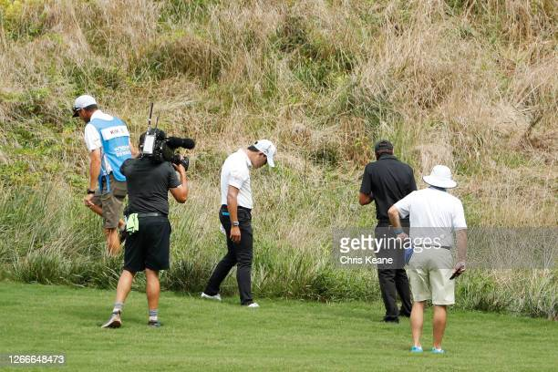 Si Woo Kim of South Korea searches for his ball on the sixth hole during the final round of the Wyndham Championship at Sedgefield Country Club on...