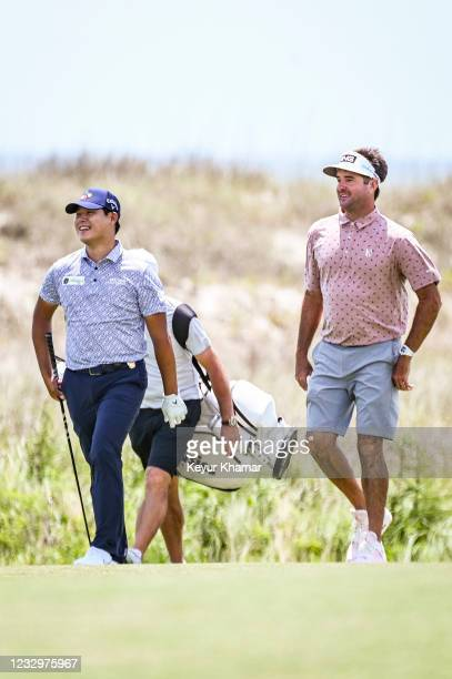 Si Woo Kim of South Korea smiles with Bubba Watson as they walk on the 18th hole during practice for the PGA Championship on The Ocean Course at...