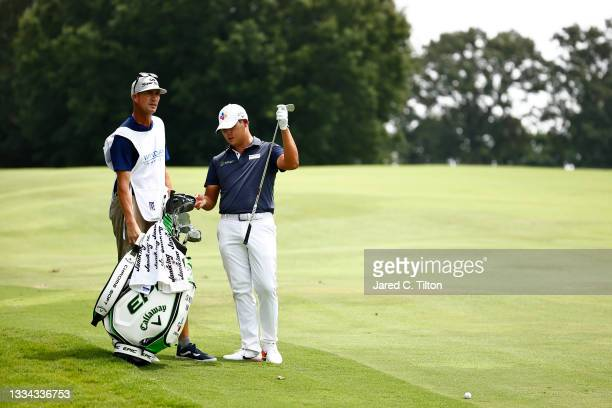 Si Woo Kim of South Korea waits with his caddie Brian Vranes before hitting an approach shot on the 18th hole during the final round of the Wyndham...