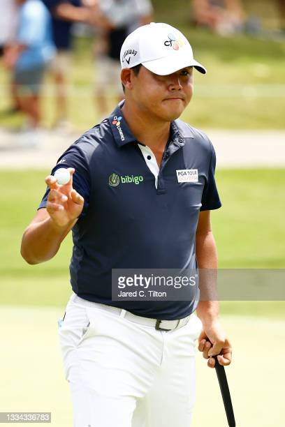 Si Woo Kim of South Korea waves after making a birdie on the 17th green during the final round of the Wyndham Championship at Sedgefield Country Club...