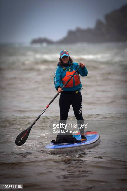 Sian Sykes from the Surfers Against Sewage campaign group surfboarding at Trearddur Bay Ynys Mon