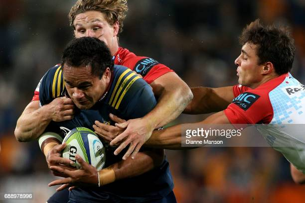 Siate Tokolahi of the Highlanders tries to break the tackle of Michael Hopper and Nick Phipps of the Waratahs during the round 14 Super Rugby match...