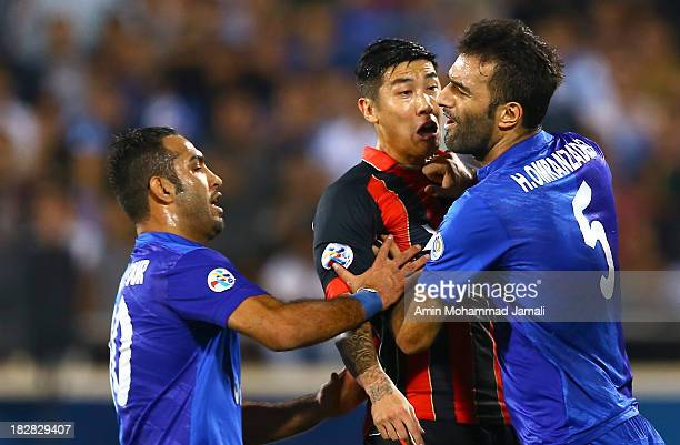 Siavash Akbarpour and Hanif Omranzadeh of Esteghlal clash with Kim Ju Yong of FC Seoul during the AFC Champions League Semi Final match between...