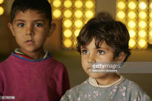Siba and her brother Abdel Kader stand inside the alMustafa mosque in Baghdad 16 November 2004 Both children fled the devestated city of Fallujah...