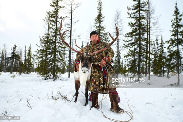 Siberian herder with reindeer in forest