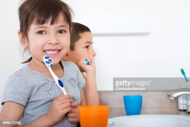 Sibling brushing teeth together