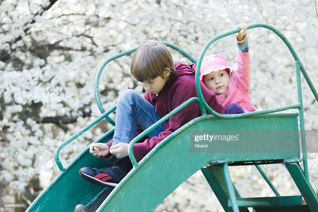 Sibling children sitting on playground slide in blossoming spring garden : Stock Photo