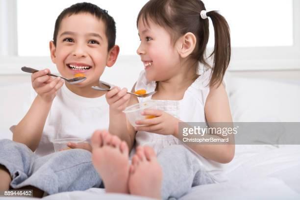 Sibling eating fruit cup in bed