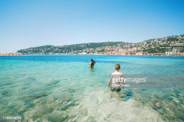 sibling having fun at beach with clear water in nice,france - nice frankrijk stockfoto's en -beelden