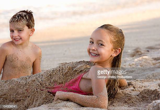 Sibling kids play in the sand at beach
