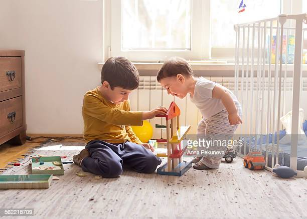 Sibling playing together with wooden toy