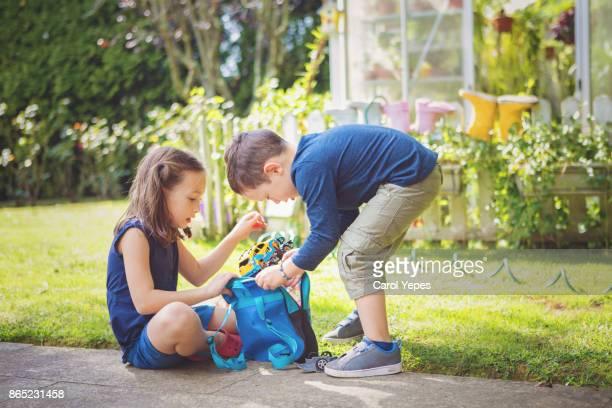 sibling playing  with car and toys in backyard