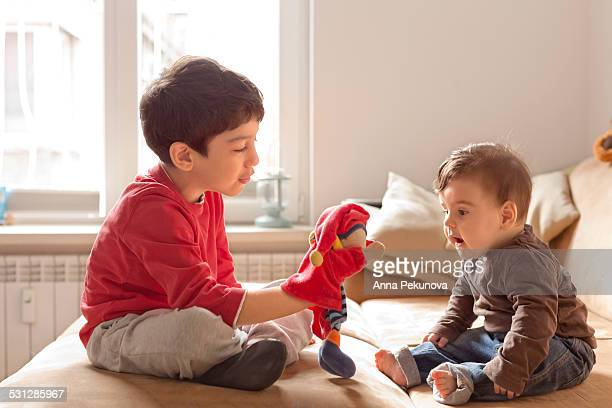 Sibling playing with hand puppet
