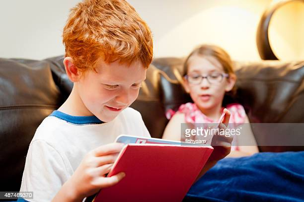 2 sibling read a book together on a couch.