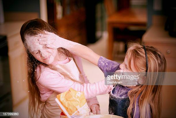 sibling rivalry -food fight - children in the kitchen series - girl fight stock photos and pictures