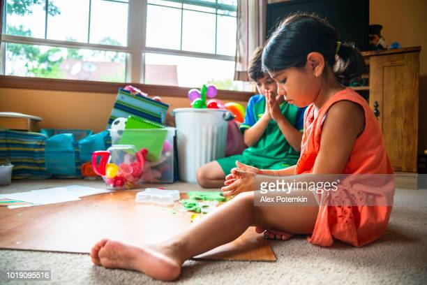 Sibling. The little brother and sister, the 8-years-old boy and 6-years-old girl, playing with the green colored toy sand on the floor in the children's room