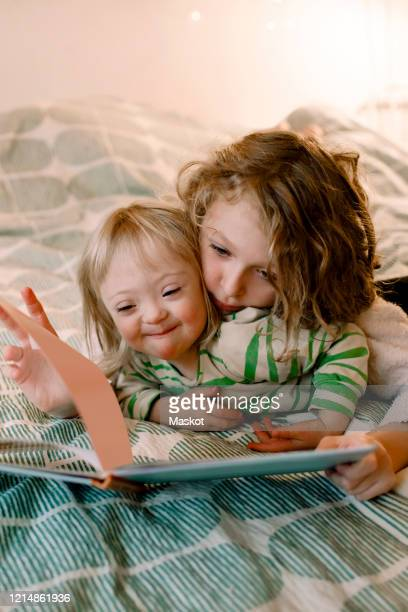sibling turning book page while lying with disabled sister in bedroom - disabilitycollection stock-fotos und bilder